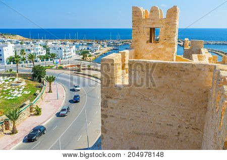 The modern white neighborhood and yacht port behind the old tower of Ribat Monastir Tunisia. stock photo