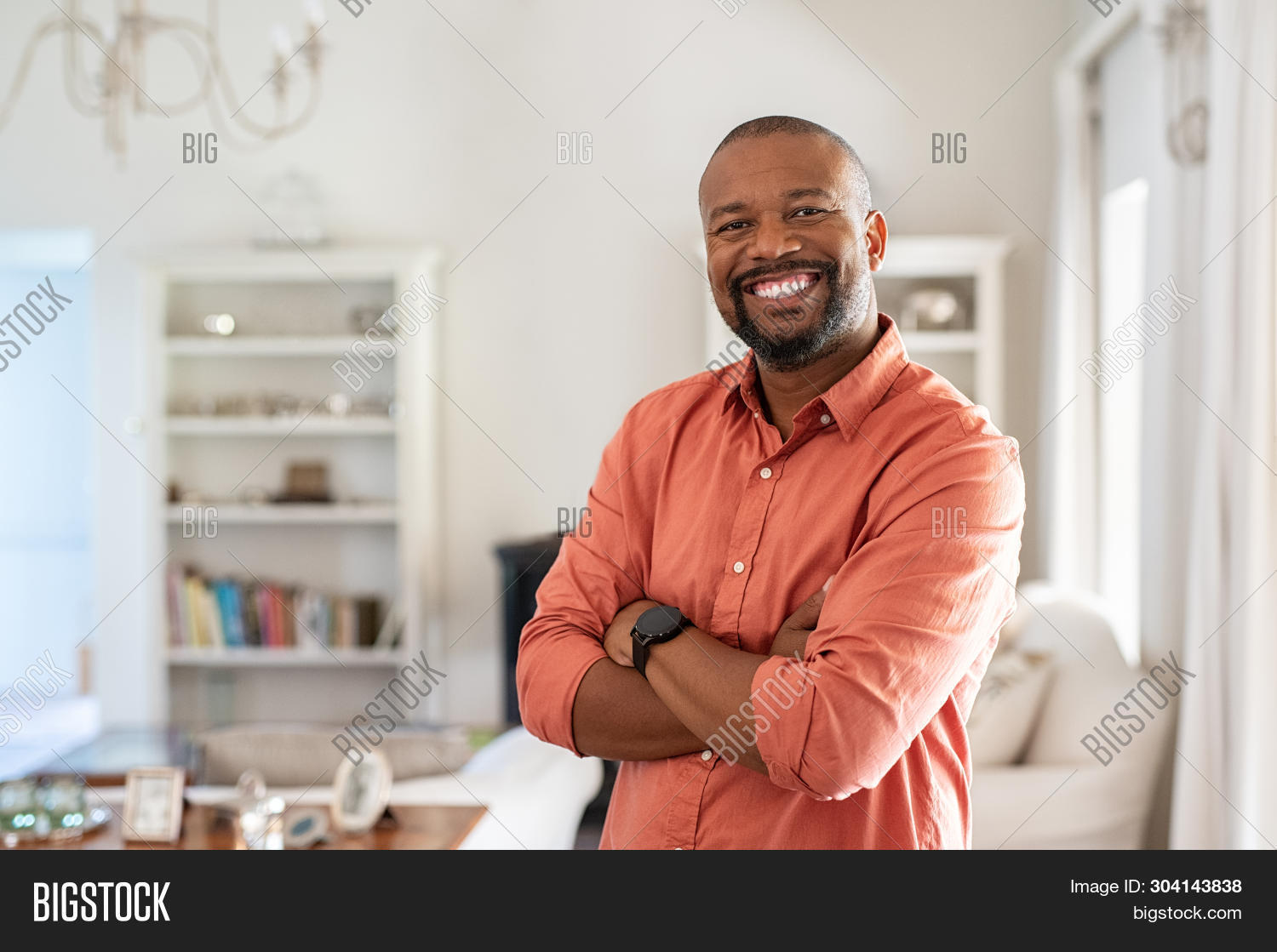 Portrait of smiling mature man with beard standing with crossed arms. Confident african man with fol