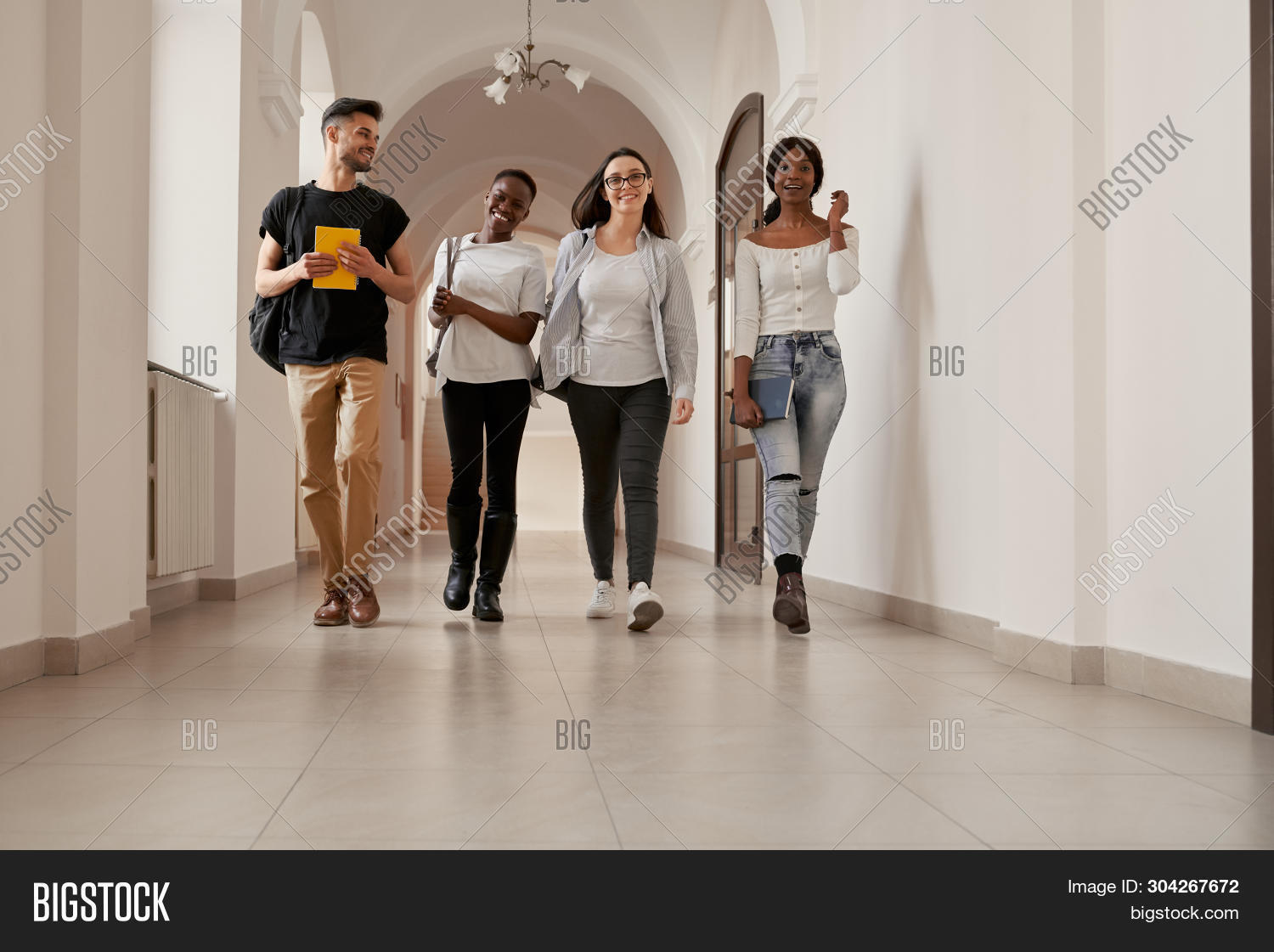 Positivity Group Of Young And Stylish Students Going Home From Lecture On Long Corridor. Happy Afric
