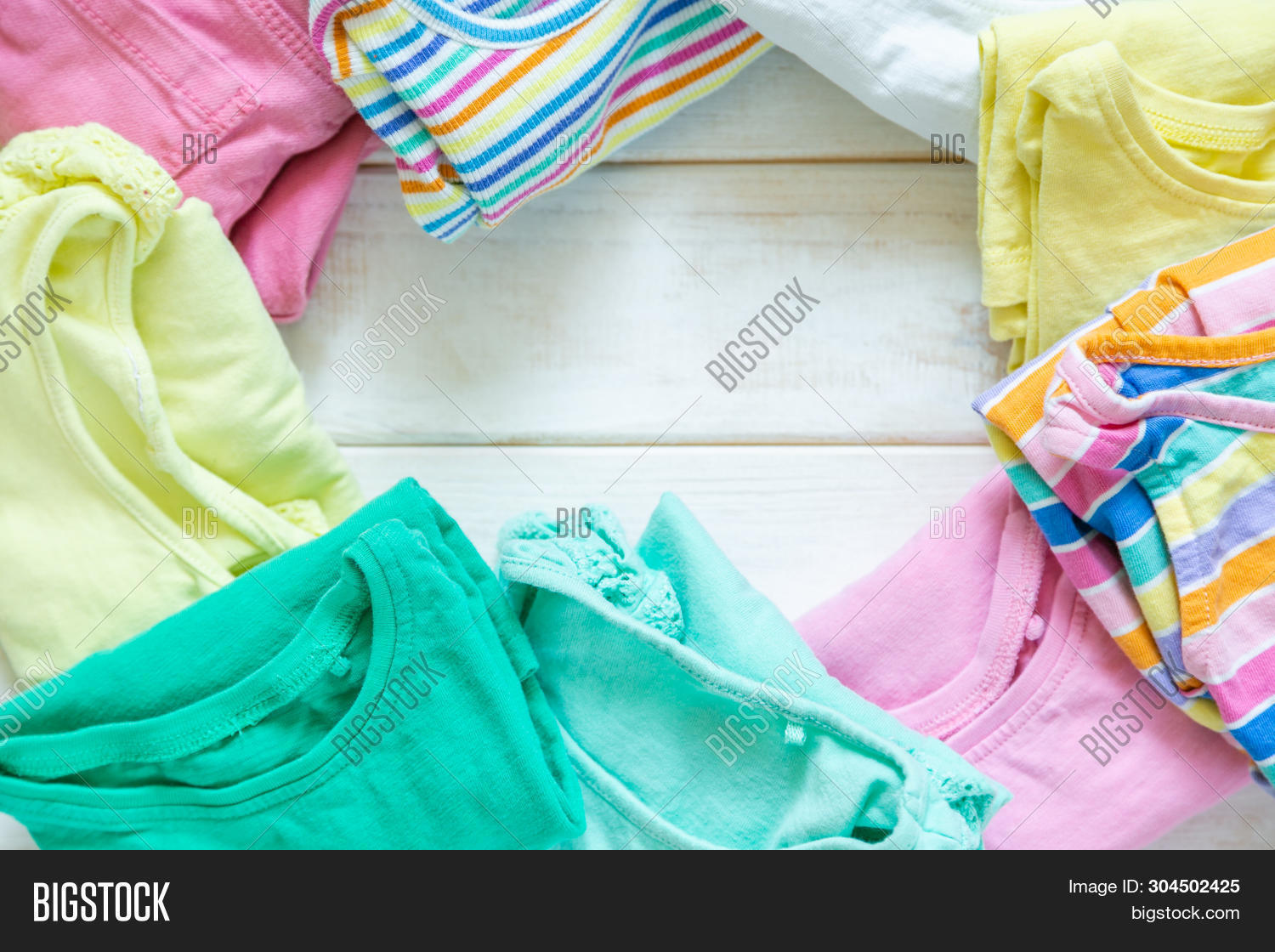 Marie Kondo Tyding Up Method Concept - Folded Kids Clothes In Pastel Colors, Copy Space