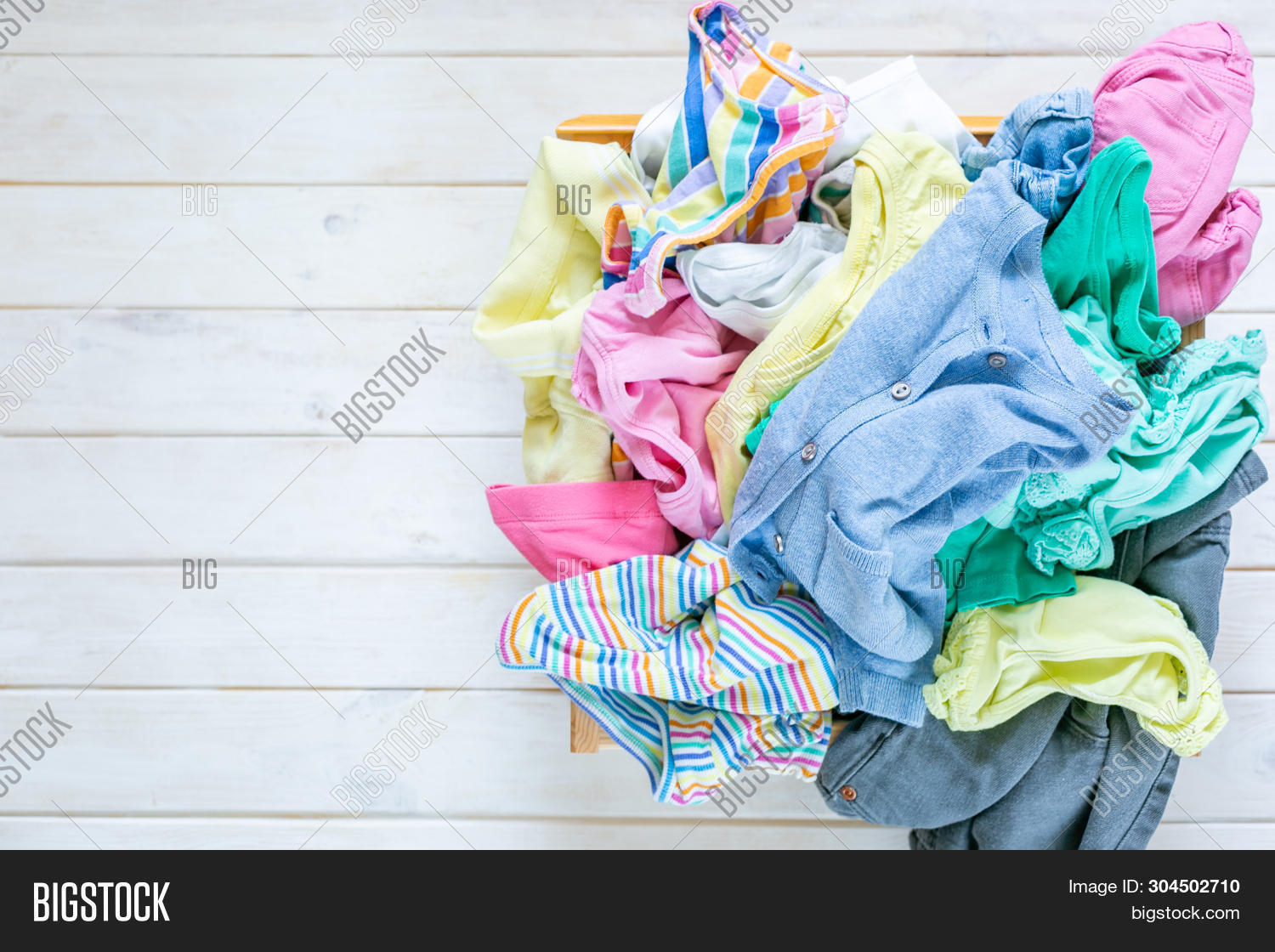 Marie Kondo Tyding Up Method Concept - Unfolded Kids Clothes In Pastel Colors, Mess, Copy Space