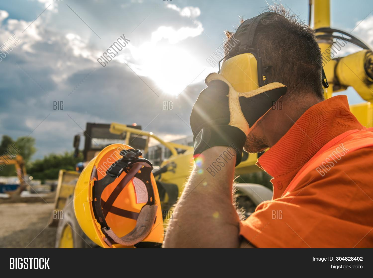 caucasian,construction,contractor,day,development,driver,har,hard,head,headphones,healthy,hearing,helmet,industrial,industry,loud,loudness,machine,machinery,noise,operator,professional,protection,protective,reduction,safety,sound,sunny,technician