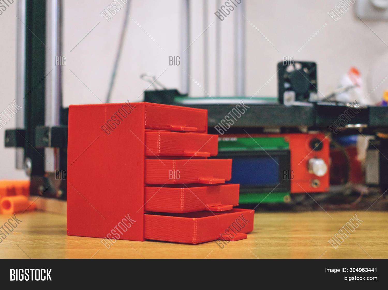 3d Printed Red Plastic Dresser On The Background Of Three Dimensional 3d Printer. Furniture Model Pr