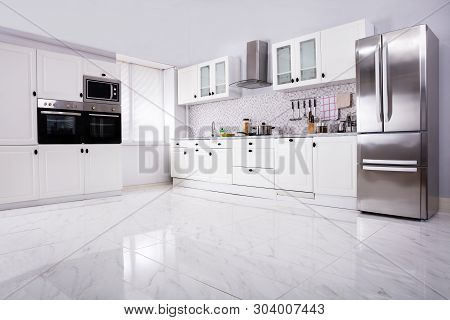 Interior Of Modern White Clean Kitchen With Microwave Oven And Refrigerator stock photo