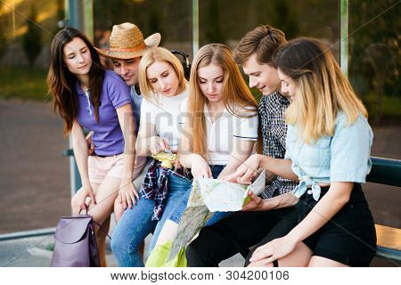 Traveling, sightseeing, group travel, city tour, togetherness. Tired tourists rest at bus stop searching the location on city map stock photo