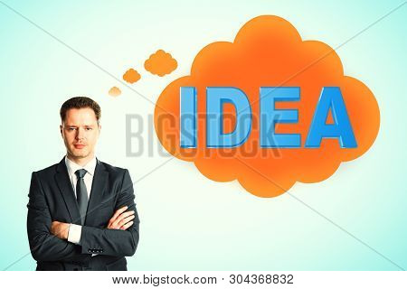 Attractive young european businessman thinking about idea on blue background. Inspire and achieve concept stock photo