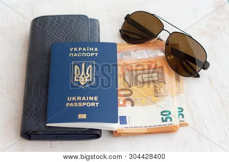 Travel and holidays in Europe or abroad. Ukraine passport for traveling in Europe against the background of Euro banknotes. stock photo