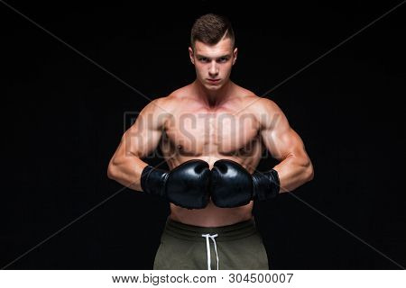 Muscular young man in black boxing gloves and shorts shows the different movements and strikes in the studio on a dark background. Strong Athletic Man - Fitness Model showing his perfect body. Copy Space. stock photo