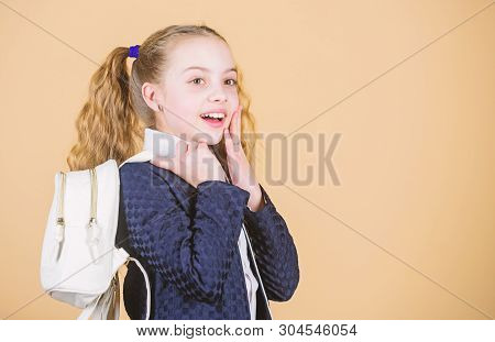 Popular useful fashion accessory. Schoolgirl ponytails hairstyle with small backpack. Carrying things in backpack. Learn how fit backpack correctly. Girl little fashionable cutie carry backpack stock photo
