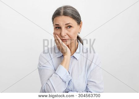 Frustrated female pensioner in blue shirt holding hand on her face having worried uneasy facial expression, thinking about her future. Unhappy sad senior woman suffering from terrible toothache stock photo