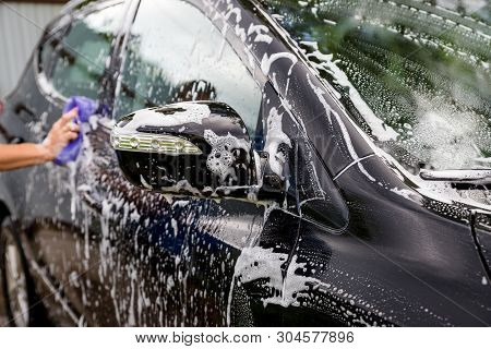 hands hold sponge for washing car.Car detailing or valeting concept. Selective focus. Car detailing. Cleaning with sponge and cloth. Worker cleaning. Auto wash concept solution to clean stock photo