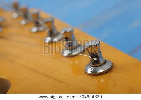 Musical instrument - Fragment headstock peghead neck tuning peg electric guitar on a blue wood background. stock photo