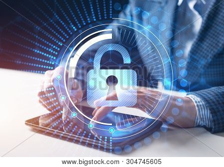Computer security concept and information technology. Risk management and professional safeguarding of cyberspace. Virtual padlock blue hologram and human hands with tablet computer on background. stock photo