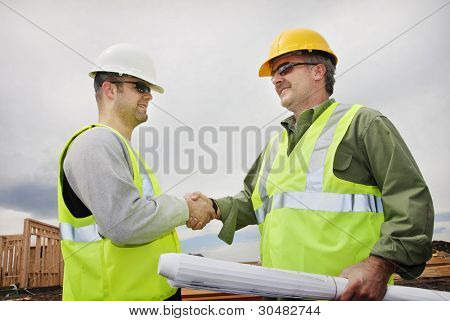 Two Construction Professionals Shaking Hands at the jobsite stock photo