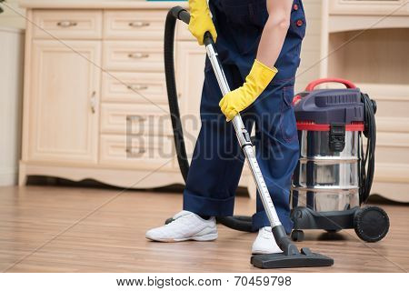 Selective focus on janitor wearing blue overalls vacuuming the floor in the office. Commode on background stock photo