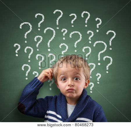 Child scratching head with question mark on blackboard concept for confusion, brainstorming and choice stock photo