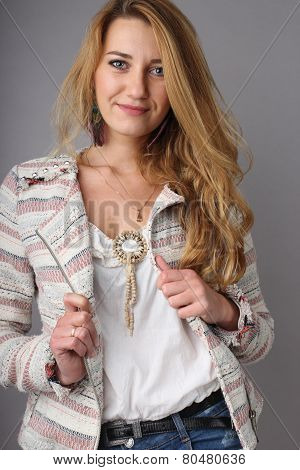 studio portrait of the young girl with a long fair hair of 25 years in a white blouse and a jacket on a neutral background, hands on hold a jacket, looks at the viewer stock photo