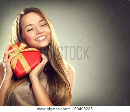 Beauty happy girl with Valentine Gift box. Smiling surprised model girl takes heart shaped red prese