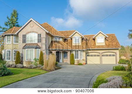 Custom built luxury house with nicely trimmed front yard, lawn in a residential neighborhood.