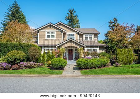 Luxury house with nicely trimmed front yard lawn in a residential neighborhood. Home exterior.