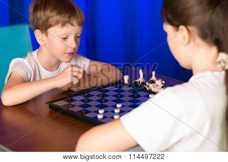 Children play a board game called checkers. Passes blitz. stock photo
