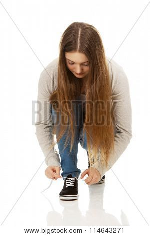 Teen woman tie shoes. stock photo