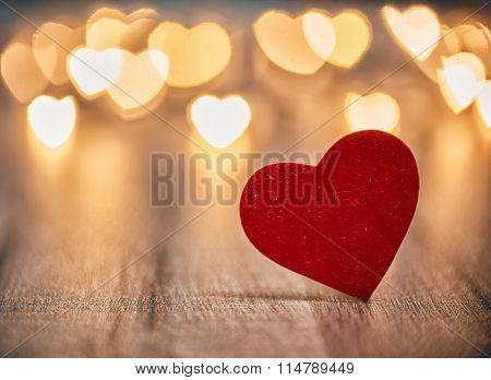 Garland lights on wooden rustic background. Valentine's day background with hearts. The concept of l
