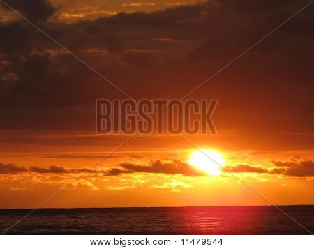 Sunset landscape from a beach in Brasil which is well known for it´s beautiful and tropical scenery. The sun and the clouds appear taking the viewer immediately to the warmth of this beautiful senary. stock photo