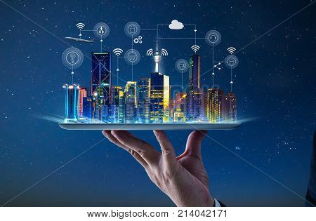 Waiter hand holding an empty digital tablet with Smart city with smart services and icons internet of things networks and augmented reality concept night scene .