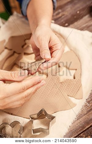 Close-up of women potter from rolled-out clay with a mold carves toys and equips them with edges in the background of clay and shapes stock photo