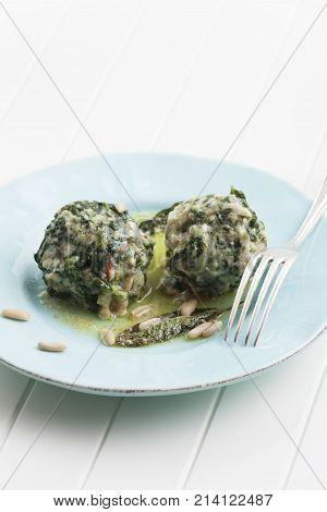 two italian strangolapreti spinach dumplings on a plate stock photo