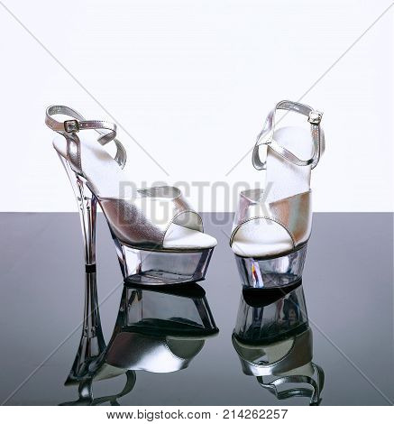 Silver transparent stripper shoes on a mirror and white background stock photo
