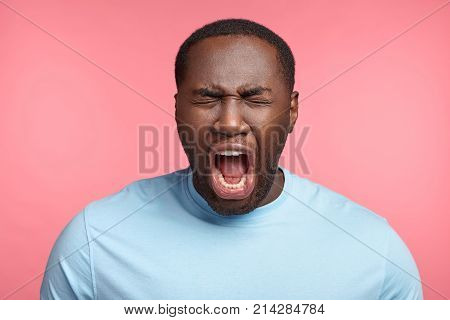 Dark skinned emotional male screams or yells opens mouth widely closes eyes being in panic or stressful situation horrified to see hear something. Negative emotions and expressions concept stock photo