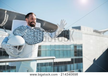 Cheerful excited spaceman is standing near guard rail and looking ahead with smile. He waving to someone. Waist up portrait. Copy space on right side stock photo
