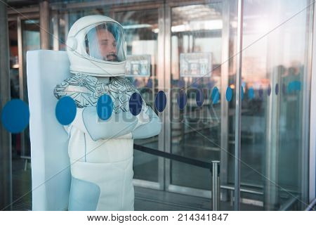 Welcome back home. Proud spaceman standing behind transparent wall and looking forward with pride. Waist up portrait. Copy space on right side stock photo
