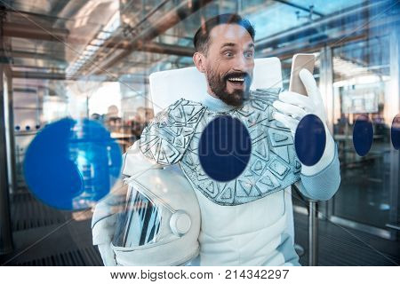 Full of wonder. Curious spaceman locating near glass wall and using device he looking at with crazy smile. Waist up portrait. Copy space on left side stock photo