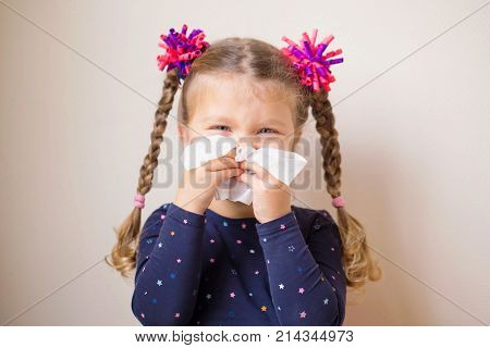 The little girl has a runny nose and blows her nose into a paper handkerchief. Children's cold selective focus on a handkerchief. Acute respiratory viral stock photo