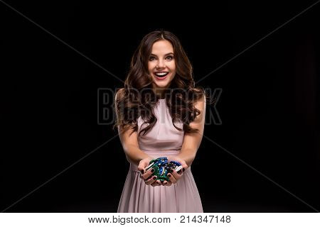 Female Poker player with paint black nails hold her poker chips to make a bet. Gambling and casino business concept. Studio shot on a black background. Casino