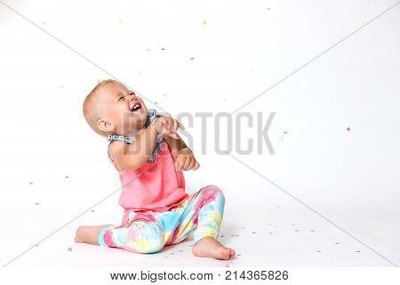 Laughing toddler girl is sitting on the floor and looking up at the paper confetti falling on her. All on a white background.