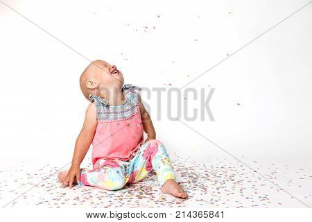 Laughing toddler girl is looking up at the paper confetti falling on her. All is on the white background.
