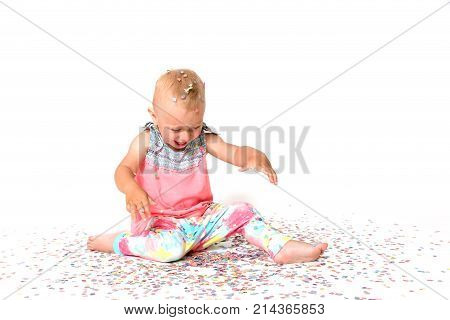 Laughing toddler girl is looking at the floor on fallen paper confetti. All on a white background.