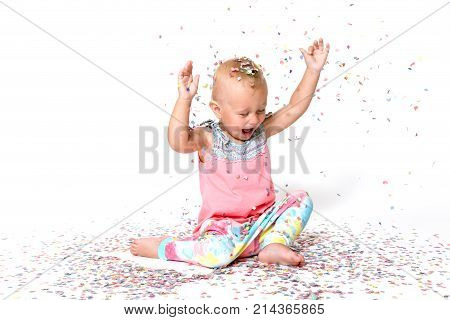 Laughing toddler girl with raised hands is looking at the floor on falling paper confetti. All on a white background.