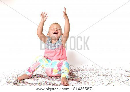 Laughing toddler girl is sitting on the floor with her arms raised. Paper confetti are fallen around her. All on a white background.