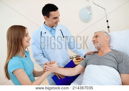 An elderly man lies in a hospital room on a bed. He is undergoing rehabilitation. Next to him is a doctor. The girl came to see the old man. They are all smiling.