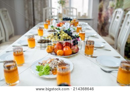 All ready for dinner, salad, fruits, sweet sea-buckthorn juice in glasses standing on a white table in the dining room