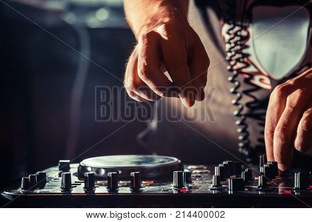 Disc jockey at the turntable. DJ plays on the best, famous CD players at nightclub during party. EDM, party nightlife concept. Dj hands on the turntables. stock photo