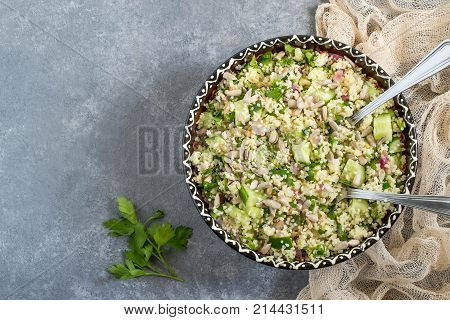 Bowl with couscous cucumber parsley sunflower seeds and sesame on gray background. Dietary and healthy food. Top view stock photo