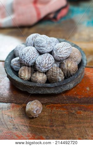 Tasty winter spice whole dried nutmeg used as an ingredient in many dishes eggnog mulled wine close up on old wooden table close up stock photo