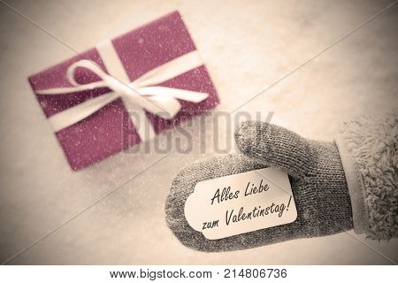 Glove With Label With German Text Alles Liebe Zum Valentinstag Means Happy Valentines Day. Pink Or Rose Gift Or Present On Snow In Background. Greeting Card With Snowflakes And Instagram Filter