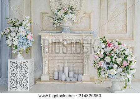Decorative fireplace with flowers and candles near brick wall in the room free space. Floral decoration of white flowers and greenery in vase over white fireplace stock photo